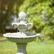Fontana in pietra in primo piano con sfondo verde