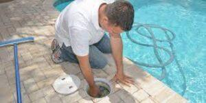 Uomo che compie la pulizia del filtro della piscina