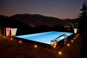 giardino con piscina con l'illuminazione